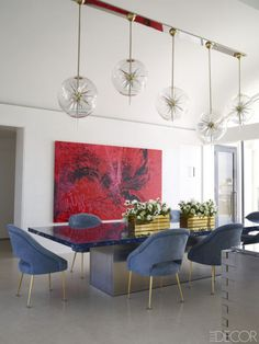 At an art-filled penthouse in Palm Beach, the dining room chairs include two originals by Maison Leleu, from Maison Gerard, as well as reproductions, all covered in a nubuck from Cortina Leathers; the resin-top table is a custom design, the painting is by Christian Marclay, and five Italian pendants form a single light fixture. Tour the rest of the home.