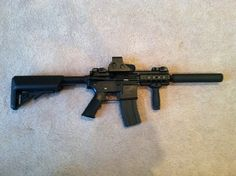 My Airsoft Gun :P  You mad bro?   So this is what my gun looks like at the moment. I don't need to do anything from here on in with the look, and the internals besides clean the barrel and such.   But I'm really happy with it. It's an Echo 1 Troy M4 with a vertical grip, G&P Holo Sight, and a 180mm suppressor. Not only is it perfect for indoors and outdoors, it's ROF is pretty solid firing 16 bb's a second.   Enjoy :)