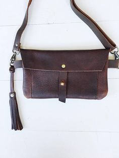 The versatile brown leather fanny pack is a great way to go hands free. This leather hip bag is perfect for biking around town, festivals, fairs, concerts and farmers markets. Created with a simple timeless design which blends with any style and made from beautiful full grain oiled and waxed leather and will patina beautifully over time. The bag closes with a Sam Browne button. The inside is all leather. -can carry a phone, cash, cards plus a few other essentials -can be worn on your hip…