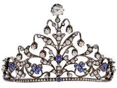 An Antique Sapphire and Diamond Tiara.  The petite tiara of triangular peaked design extending from a narrow band, the floral and foliate motifs with rose-cut diamond leaves amid sapphire florets and buds, further embellished by suspended old mine-cut diamond drops, the apex enhanced by a larger rose-cut diamond, mounted in silver and 18k gold, French assay marks, with fitted box, late 19th century
