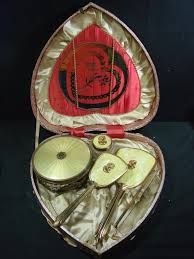 """Heart shaped case containing a 7 piece vanity set with cameo detail. You can """"Buy It Now"""" for $149.99 over at deophamdealers on eBay."""