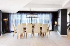 Luxe dining room with dark walls and large pendant light. Large timber dining table and light upholstered chairs, grey sheer curtain.