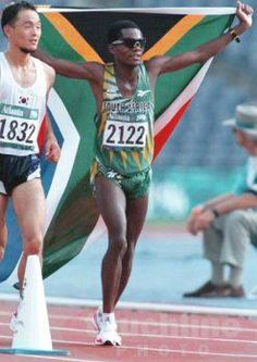 Josiah Thugwane proudly holds the South African flag aloft after winning gold in…