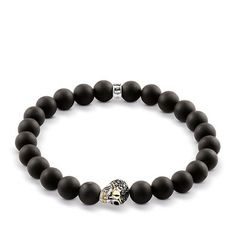 The visual highlight of this #THOMASSABO stretch bracelet crafted from matt-black obsidian beads is a design innovation with an ironic wink: the bentre bead, a black and white #diamond-embellished skull crafted from blackened 925 Sterling silver, features a filigree eye-patch and an 18k yellow gold smile.