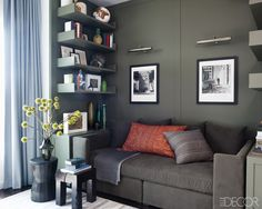 In the study, a Calvin Klein Home sofa is topped with vintage Moroccan  pillows, the stools are by Tucker Robbins, left, and Oly, and the light fixtures are from Circa Lighting; the custom-made paneling and shelves are painted in Benjamin Moore's Dark Olive.   - ELLEDecor.com