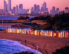 Australia, Australia + Pacific: The Melbourne skyline rises behind the colorful bathing boxes on Brighton Beach.
