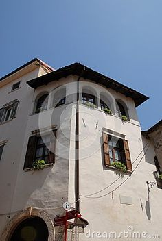 Photo made in the province of Trento in Rovereto (Italy). The picture shows a part of a simple but ancient building in the center. Particularly interesting are the five windows at the top near the roof that suggest an interior bright and beautiful.