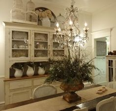whitewashed color scheme and sparkly chandelier.  Rustic table and hutch.  Love the contrast.