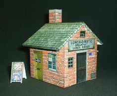 Lunch-O-Matic Restaurant Paper Model - by Papermau - Here a little (just one page) and easy-to-build paper model of a imaginary restaurant, in 1/35 scale. In the arquive you will find more two little buildings and a blank template, to you design your own little house. - Download this free and exclusive paper model at Papermau!