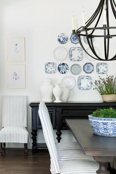 Blue decorative plates hang over an antique black buffet table placed facing an espresso stained balustrade dining table lit by an iron chandelier and seating white and blue striped slipcovered dining chairs.