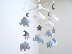 This baby mobile features 6 baby elephants in light blue and gray and hanging in the middle is a mother elephant in light blue and gray with a