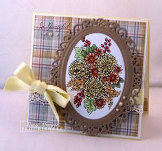 like the color pallet with the plaid background, fancy brown frame and autumn colors for the flowers...