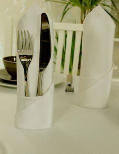 Weiße Stoffservietten mit einem leichten glanz sorgen für ein festliches…