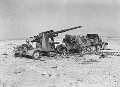 A destroyed Famo 18 with an 88mm Flak gun out of action in North Africa.