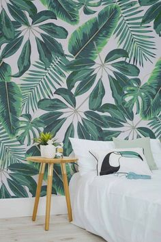 Dormitorio sin cabecero con pared decorada con papel pintado de estilo tropical.