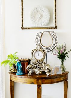 White walls, gold framed mirror, wooden stand with an assortment of art pieces