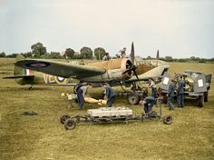 Bristol Blenheim Mark IV, R3600, of No. 110 Squadron RAF, undergoes an elaborate servicing for the photographer at RAF Wattisham, Suffolk. Armourers unload 250lb GP bombs and Small Bomb Containers (SBCs) of incendiaries from a trolley, while other ground-crew refuel the aircraft and attend to the engines, the cockpit and the gun-turret, accompanied by a pet dog on the engine cowling. June 1940