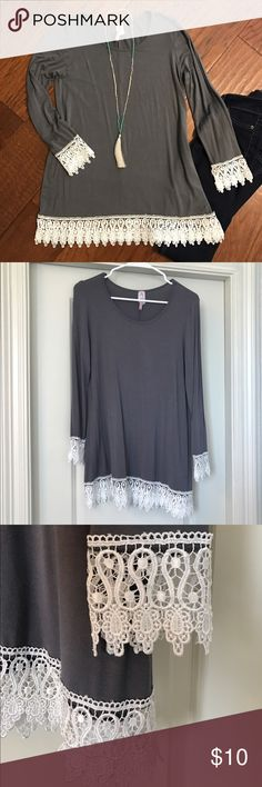 Lace Hem Tunic Gray Tunic with white lace hem around bottom and wrists. One torn piece of lace on bottom left of shirt hem as shown in last photo. Not noticeable when worn. Loose fit. Tags removed, lightly worn. Purchased at a boutique. Moa Tops Tunics