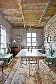Old country house kitchen with wooden chairs and bench with large wooden dinner table. Finland.