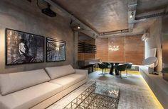CASA COR BAHIA 2014. Ambiente: Studio Manhattan. A arquiteta Larissa Grimaldi se inspira nos lofts novaiorquinos ao enfatizar o aspecto brutalista do concreto, o mobiliário no estilo industrial, as eletrocalhas e as tubulações aparentes. Predominam os tons de cinza, aquecidos pela madeira no painel (Oca Brasil) e nas persianas (Hunter Douglas). As cadeiras em couro verde escuro adicionam um toque de cor, enquanto os muranos brancos com pó de ouro e o tapete de seda do Nepal pontuam com…