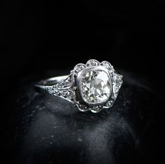 WOW! A beautiful and unique old-mine cushion cut diamond engagement ring, set in platinum and adorned with diamonds and milgrain.
