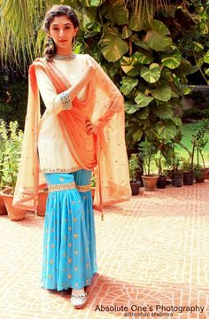 Turquoise blue embroidered sharara with a yellow kurta and peach dupatta.