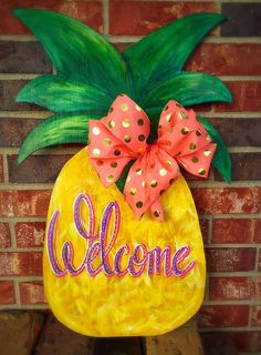 """Fun, summer door decor. This wooden pineapple door hanger is a bright welcome to any entry way, front/back porch or kitchen. Wood and paint is finished with a sealer to make this hanger weatherproof for outdoor use. Measures 16""""x24"""" 