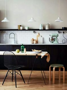 Black kitchen with white subway tile splash back.