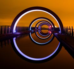 A more cropped view of the iconic Falkirk Wheel - a rotating riverboat lock in Falkirk, Scotland. At night it lights up and the metal arches slowly chan. The Falkirk Wheel glows Places To See, Places To Travel, Falkirk Wheel, England And Scotland, Scotland Uk, Wanderlust, Scotland Travel, Light Art, Great Britain
