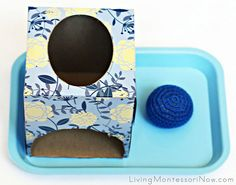 DIY home-made Montessori Object Permanence Box Made from a square tissue box with hole cut in one side's bottom area