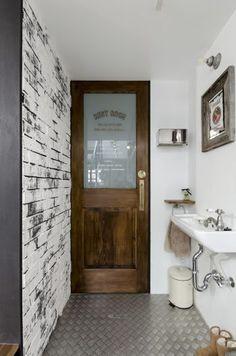 トイレの扉の文字は勇介さんデザインのカッティングシート。左の壁は黒いブリックタイルを張った上から漆喰を塗った。