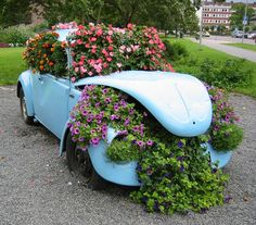 The little VW Beetle loaded down with very pretty flowers. All ready to go, but can't go.....got a flat tire!! Love this!!