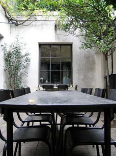Black table, black chairs in a simple courtyard space. Pinned to Garden Design - Courtyards by Darin Bradbury.