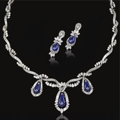 HIGHLY IMPORTANT KASHMIR SAPPHIRE AND DIAMOND DEMI-PARURE, 1960S Comprising: a necklace and a pair of pendent earrings, each composed of tear drop sapphires set within stylised ribbon surrounds of marquise- and pear-shaped and baguette diamonds, each studded with a brilliant-cut stone, mounted in platinum