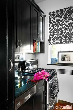 """In a Manhattan apartment, the existing kitchen cabinets were painted Benjamin Moore Aura in Black. """"I wanted it to look less boring and more like a smart butler's pantry,"""" designer Lilly Bunn says. Roman shade in Holland & Sherry's Belfour linen.   - HouseBeautiful.com"""