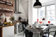 Small kitchen with exposed brick and concrete table