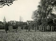 """De Joodse begraafplaats, hier als overgebleven deel van de voormalige Algemene Begraafplaats aan de Singel, gezien vanuit het oosten. Let op de grafstenen met Hebreeuwse teksten (zie voor vertaling """" De Joodse Gemeente van Schiedam' door S.Ph. Louis, ongepubl.) Op de achtergrond de huizen die gelegen zijn tussen de Broersvest, west- en oostzijde. Links de toren van de Grote Kerk, rechts achter de bomen, de ruïne van Mathenesse"""