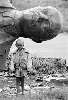 Dario Mitidieri - Ethiopia. /Boy standing in front of fallen statue of Lenin / 1991 [ ? ] / [***]
