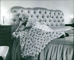 Vintage photo of Martine Carol talking on phone while lying on bed. -