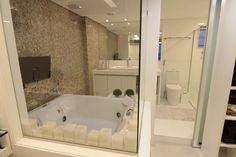 Banheiro integrado com closet, separado apenas por uma porta de correr de espelho. Área da banheira separada do closet apenas por um painel em vidro.