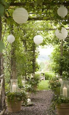 LOVE the easy -- and romantic -- effect of paper lanterns and hurricane candles under this arbor.