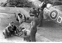 Polish Fighter Squadron Airmen watching the remains of 303 German aircraft shot down 'Ju 88'. On the right you see the plane 'Spitfire' belonging to the pilot Jan Zumbach.