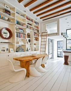 Painting wood floors with crisp white paint is also a popular choice. Here the result is just great. The wide white planks add to the fresh modern appeal and create a wonderful sense of movement against the ceiling beams running in an opposing direction.