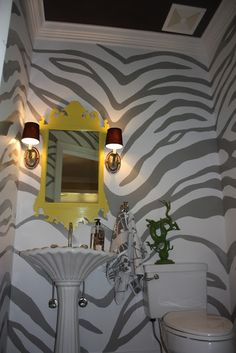 Amazing zebra painted wall.  Maybe for the closed off area where the toilet is