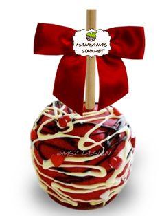 Manzana envuelta de caramelo con capa de chocolate color rojo, decorada con tiras de chocolate semiamargo, chocolate blanco y corazones de azúcar.