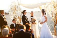 The ceremony site will feature a chuppah made from four 8ft. tall manzanita trees with lavender and fuchsia dendrobium orchids wired to the branches and the base covered in ivory fabric topped with purple hydrangeas, fuschia roses, lavender spray roses, fuchsia phalaenopsis blooms, and dendrobium orchid blooms in lavender and fuchsia with a sheer ivory tallit connected in four corners to the manzantia trees.