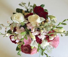 Clutch bridal bouquet designed by Sunnycrest Flowers featuring ranunculus, gerbera, lisianthus, spray stock,spray roses, hypericum berries, freesia. Lovely fragrant bouquet in this years most popular colors.  #mauveburgandycream #victoriancolors #bridalbouquet