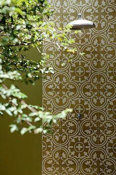 Para destacar a área do chuveirão na parede verde, a moradora escolheu o revestimento de ladrilho hidráulico, o mesmo do piso da cozinha, integrada ao jardim por portas de correr com vidro