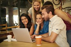 A group of friends hanging out in a coffee shop with a laptop amongst them - stock photo #1295710