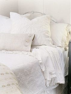 An all-white bed makes mixing patterns and textures easy.  This bed boasts at least four different textiles in different shades of white, including lace, matelasse and homespun fabrics.